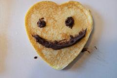 Frühstückskunst Pfannkuchen Herz mit Gesicht
