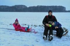Spaziergang im verschneiten Feld mit Schlitten